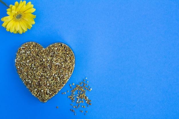 Bijenpollen in de hartvorm op de blauwe achtergrond. bovenaanzicht. kopieer ruimte.