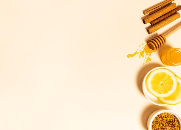 Bijenpollen; schijfje citroen; honing; honingdipper en kaneel gerangschikt in een rij op beige achtergrond