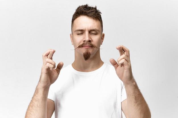 Bijgeloof en verwachting concept. foto van knappe bijgelovige jonge bebaarde hipster-man die zijn ogen sluit en zijn vingers kruist voor geluk, in de hoop dat al zijn dromen zullen uitkomen