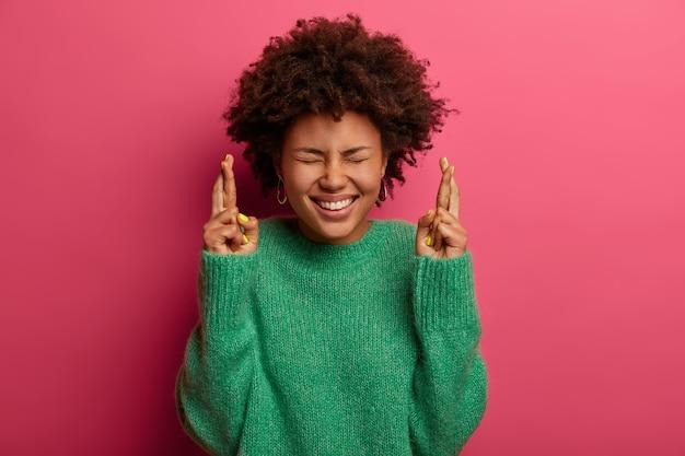 Bijgelovige afro-amerikaanse vrouw gericht op overwinning, hoopt positief resultaat te krijgen, kruist vingers en glimlacht vreugdevol, draagt groene trui, anticipeert op belangrijk nieuws, geïsoleerd op roze muur