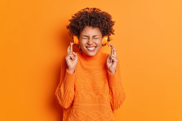 Bijgelovige jonge afro-amerikaanse tienermeisje kruist vingers gelooft in geluk doet wens terwijl luistert naar muziek via draadloze koptelefoon draagt casual trui geïsoleerd over oranje muur
