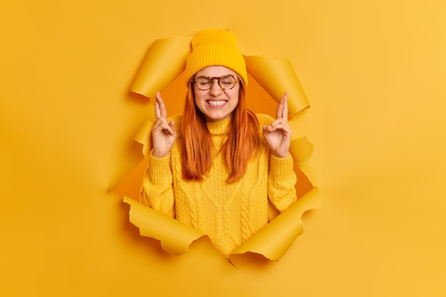 Bijgelovige roodharige vrouw klemt tanden kruist vingers hoopt dromen uitkomen draagt gele hoed en trui breekt door papieren gat. ginger millennial girl gelooft in geluk. wens concept