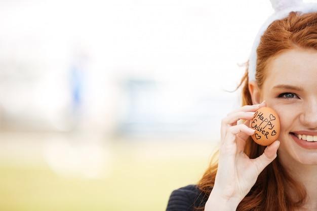 Bijgesneden afbeelding half gezicht van een jonge vrouw met rode kop