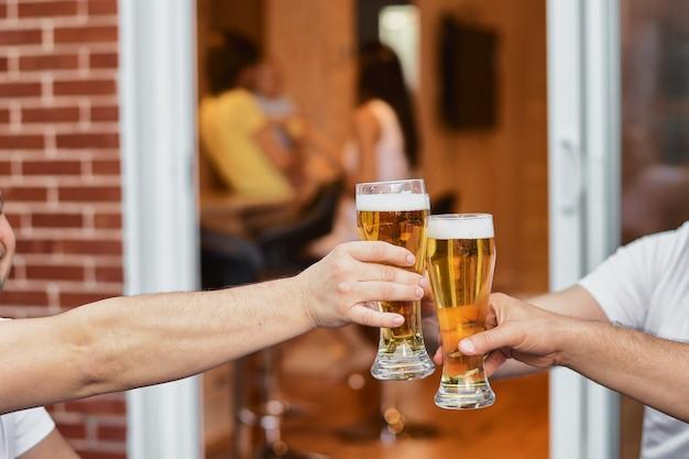 Bijgesneden afbeelding handen van een groep stemhebbende glazen bier, feesten en vieringen. bierglazen thuis op het terras van het huis