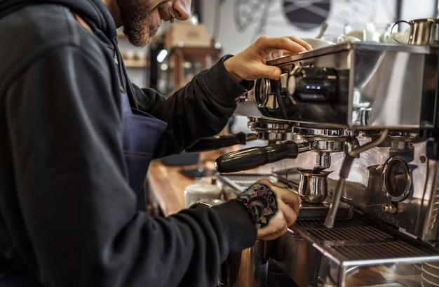 Bijgesneden afbeelding, mannelijke barista met behulp van professionele koffiemachine die van baan in café i geniet
