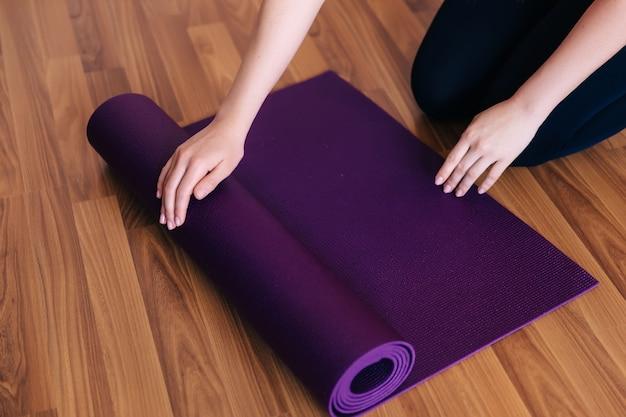 Bijgesneden afbeelding meisje dat een yogamat uitrolt om thuis te trainen