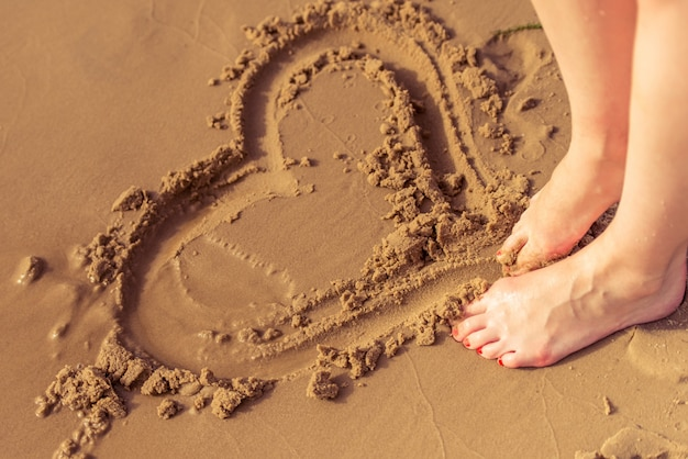 Bijgesneden afbeelding meisje hart tekening op zand van het strand.