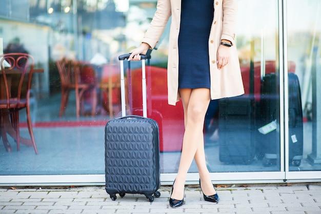 Bijgesneden afbeelding toeristische toerist vrouw gekruiste benen in de zomer casual kleding met koffer op weg in de stad buiten. meisje dat naar het buitenland reist om in het weekend te reizen. toeristische levensstijl