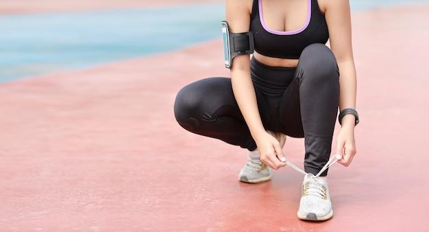 Bijgesneden afbeelding van aziatische vrouw in sportkleding joggen buiten met slanke atletische benen. sportieve meisjeshanden nemen pauze en schoen strikken. na training. gezond en lifestyle outdoor concept