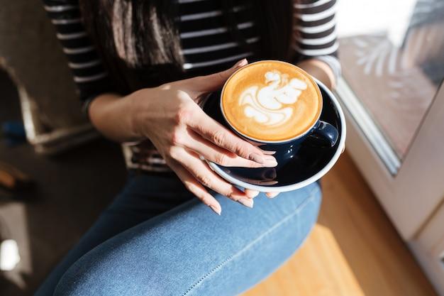 Bijgesneden afbeelding van aziatische vrouw met koffie in de buurt van het raam