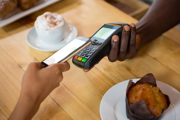 Bijgesneden afbeelding van barista betaling via mobiele telefoon accepteren in café