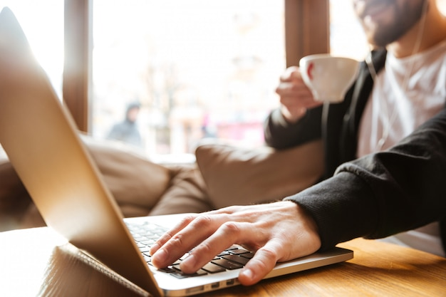 Bijgesneden afbeelding van bebaarde man in café in de buurt van het raam