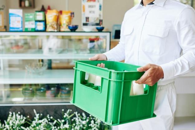 Bijgesneden afbeelding van bezorger in wit uniform plastic melkkrat naar de supermarkt