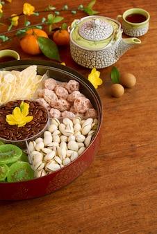 Bijgesneden afbeelding van doos met zoete snacks en theepot