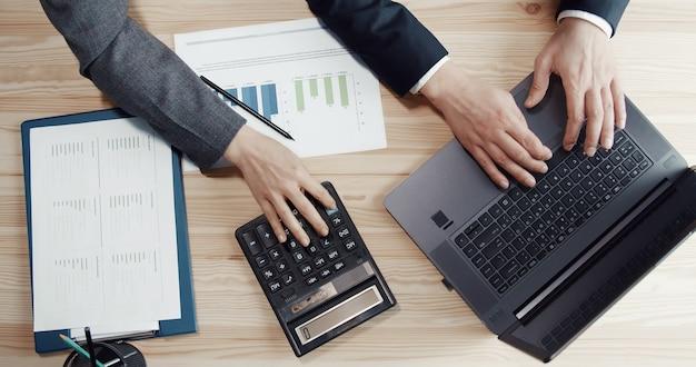 Bijgesneden afbeelding van drie handen tijdens het boekhoudproces met behulp van laptop en rekenmachine, bovenaanzicht