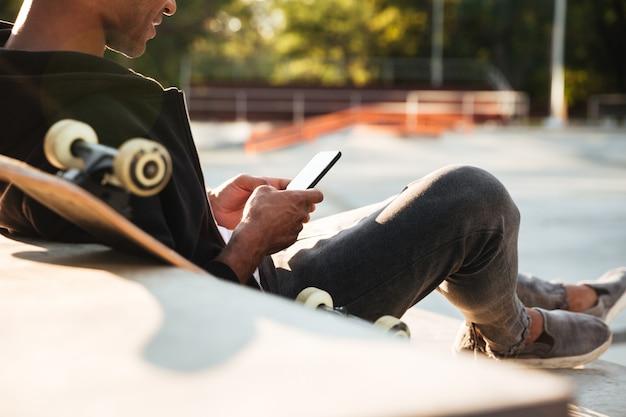Bijgesneden afbeelding van een afrikaanse man met behulp van mobiele telefoon