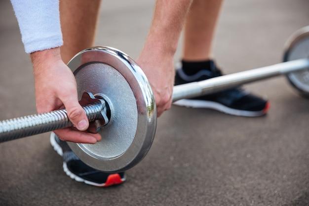 Bijgesneden afbeelding van een gespierde fitnessman die zware barbell buitenshuis gaat tillen