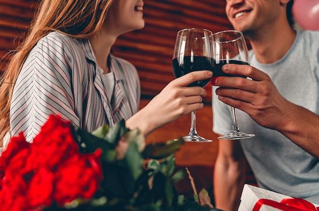 Bijgesneden afbeelding van een jong koppel in de slaapkamer met glazen wijn, cadeau en rode rozen