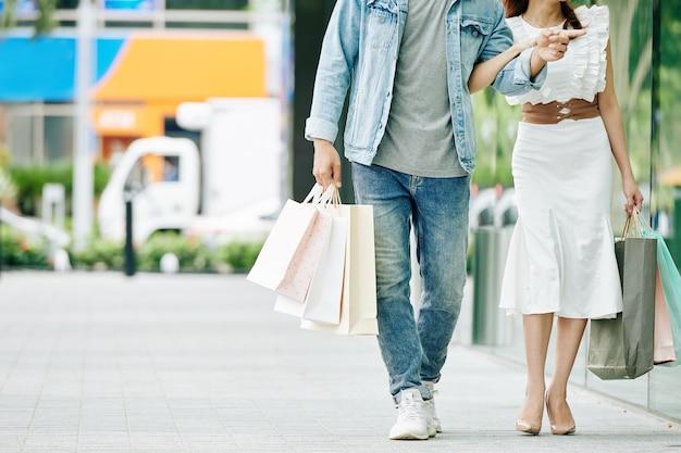 Bijgesneden afbeelding van een jong koppel met boodschappentassen die in de straat lopen
