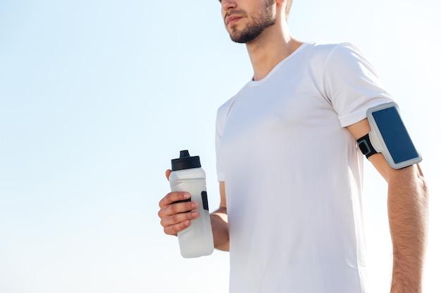 Bijgesneden afbeelding van een jonge mannelijke sportman die een waterfles buiten vasthoudt