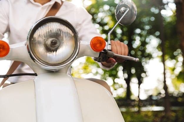 Bijgesneden afbeelding van een jonge zakenman zittend op een motor buitenshuis