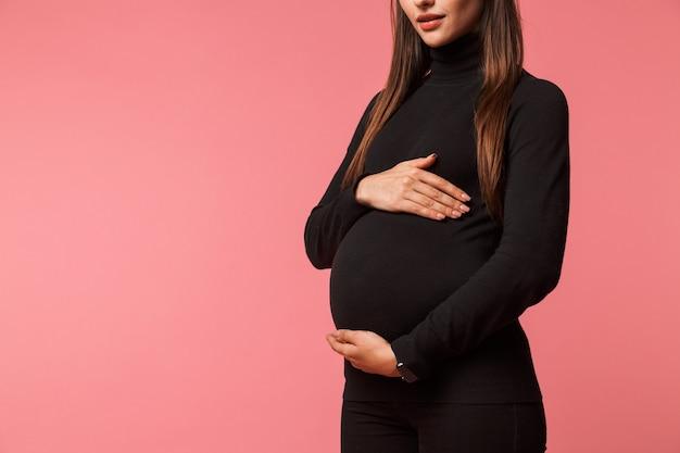 Bijgesneden afbeelding van een jonge zwangere vrouw geïsoleerd over roze, hand in hand in haar buik