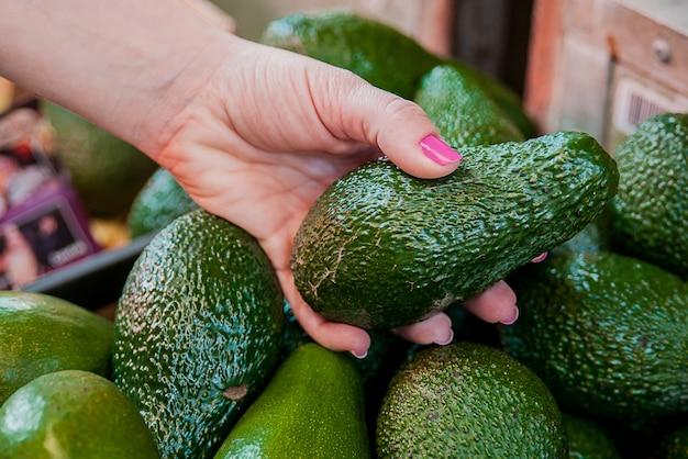 Bijgesneden afbeelding van een klant die avocado's in de supermarkt selecteert. close-up van vrouwelijke hand die avocado in de markt houdt. verkoop, winkelen, eten, consumentisme en mensenconcept