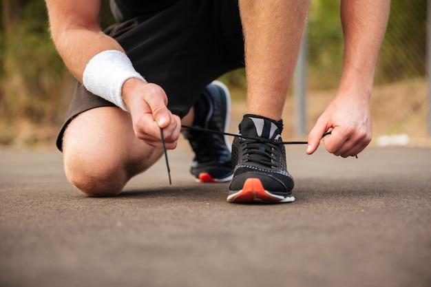 Bijgesneden afbeelding van een knappe jonge sportman die schoenveters in de buitenlucht aan zijn sneakers bindt