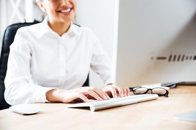 Bijgesneden afbeelding van een lachende, gelukkige zakenvrouw die op het toetsenbord typt terwijl ze aan het bureau zit