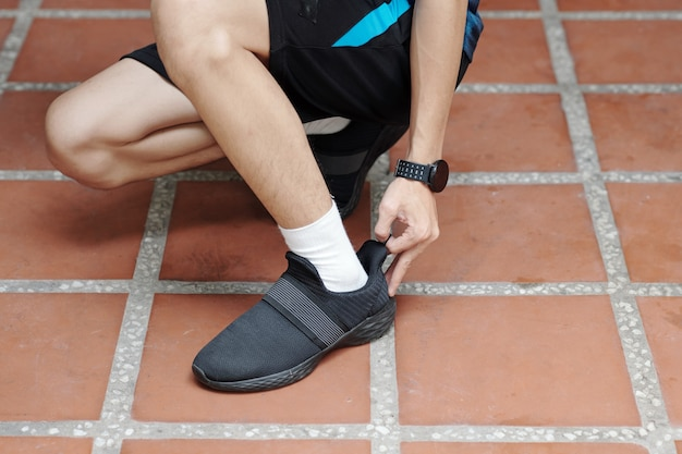 Bijgesneden afbeelding van een man die sneakers aantrekt voordat hij 's ochtends buiten jogt