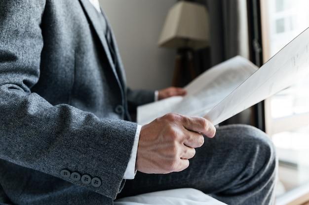 Bijgesneden afbeelding van een man in pak zitten
