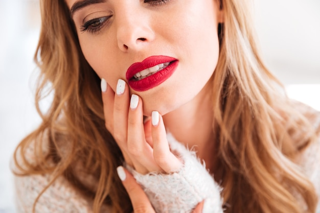 Bijgesneden afbeelding van een mooi blond meisje met rode lippenstift en lang haar
