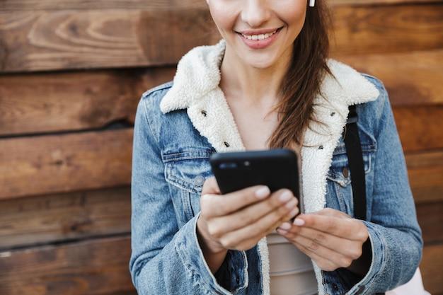 Bijgesneden afbeelding van een mooie jonge brunette vrouw jas dragen, dragen rugzak buiten lopen over houten muur, luisteren naar muziek met koptelefoon, mobiele telefoon te houden