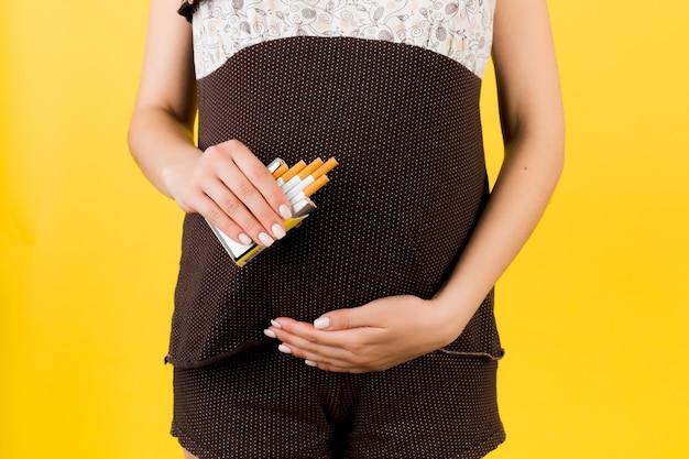 Bijgesneden afbeelding van een pakje sigaretten in handen van de zwangere vrouw op gele achtergrond. risico op abortus. rookverslaving. gevaarlijke gewoonte.