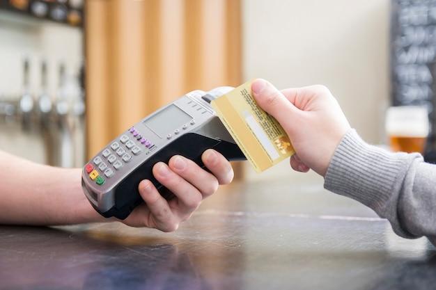 Bijgesneden afbeelding van een persoon die met een creditcard betaalt