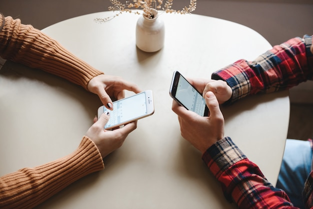 Bijgesneden afbeelding van een schattige jonge verliefde paar zitten in café binnenshuis met behulp van mobiele telefoons.
