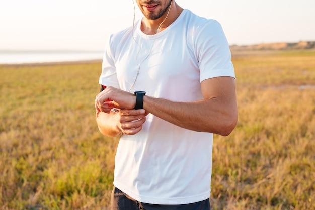 Bijgesneden afbeelding van een sportman die zijn smartwatch met oortelefoons bekijkt