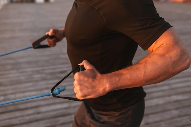 Bijgesneden afbeelding van een sterke sportman die oefeningen doet