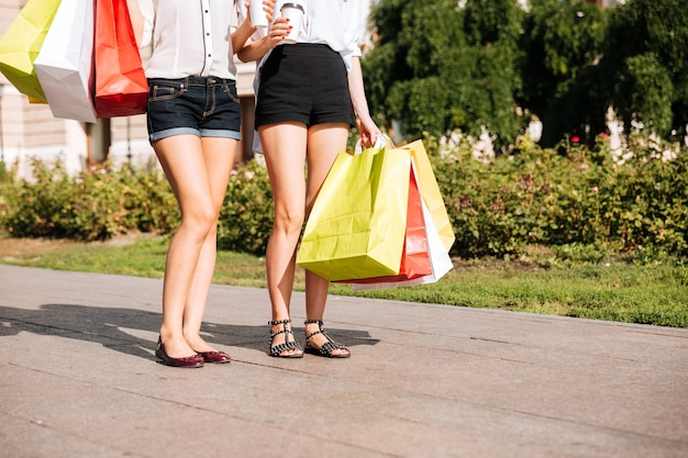 Bijgesneden afbeelding van een twee jonge vrouw die langs straat loopt met boodschappentassen en koffiekopjes