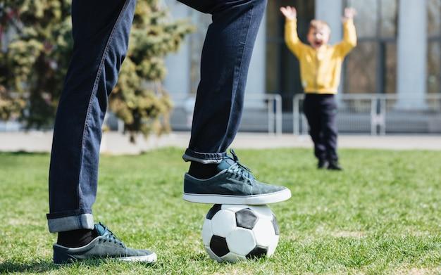 Bijgesneden afbeelding van een vader voetballen met zijn zoon