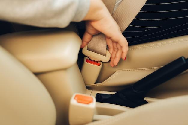 Bijgesneden afbeelding van een vrouw die in de auto zit en haar veiligheidsgordel omdoet