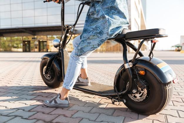 Bijgesneden afbeelding van een vrouw zittend op een motorfiets