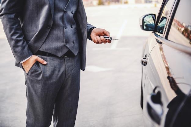 Bijgesneden afbeelding van elegante zakenman die naast zijn auto staat en sleutels vasthoudt.