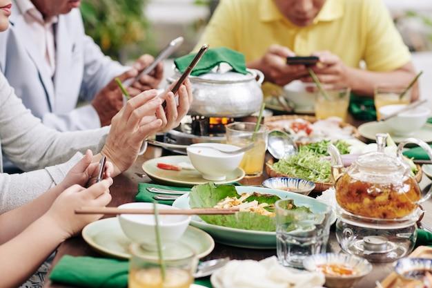 Bijgesneden afbeelding van familieleden die sociale media gebruiken op smartphones tijdens een familiediner