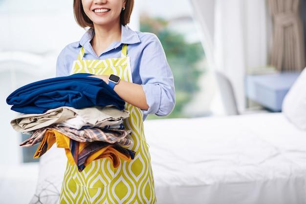 Bijgesneden afbeelding van glimlachende huisvrouw in schort bedrijf stapel kleren klaar om te strijken