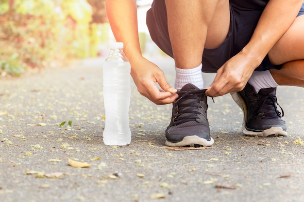 Bijgesneden afbeelding van handen gelijkmakende schoenveters op sneaker met fles water.