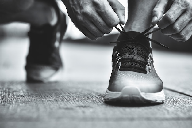 Bijgesneden afbeelding van handen schoenveters koppelverkoop op sneaker met oppervlak achtergrond handen van sportman met stappenteller schoenveters koppelverkoop op sportieve sneaker running apparatuur concept
