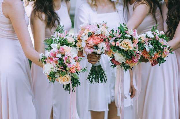 Bijgesneden afbeelding van het bruidsmeisje en de bruid van een anonieme bruid gekleed in witte satijnen toga's met prachtige bruidsboeketten. ochtend van de bruid. bruiloft bloemen details.