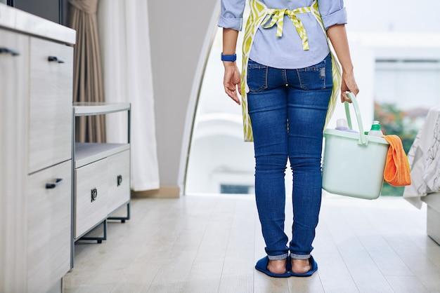 Bijgesneden afbeelding van huisvrouw in spijkerbroek permanent met emmer wasmiddel in de hand klaar om haar appartement schoon te maken