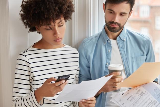Bijgesneden afbeelding van interraciale collega samenwerken voor het presenteren van informatie voor zakenpartners